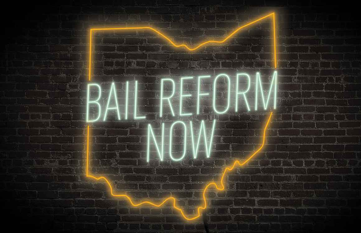 Bail Reform Now neon sign with the ourline of ohio in green and orange on a dark brick background