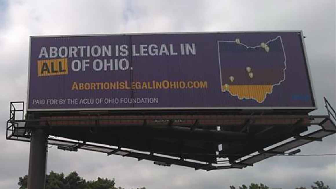 """Billboard with a purple background that reads """"Abortion is legal in ALL of Ohio"""" and includes an image of the state of Ohio with map markers showing existing abortion clinics"""