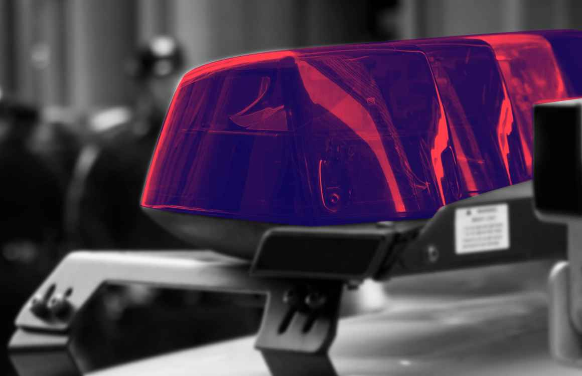 Police car lights with a navy and red color overlay, with a black and white blurry background