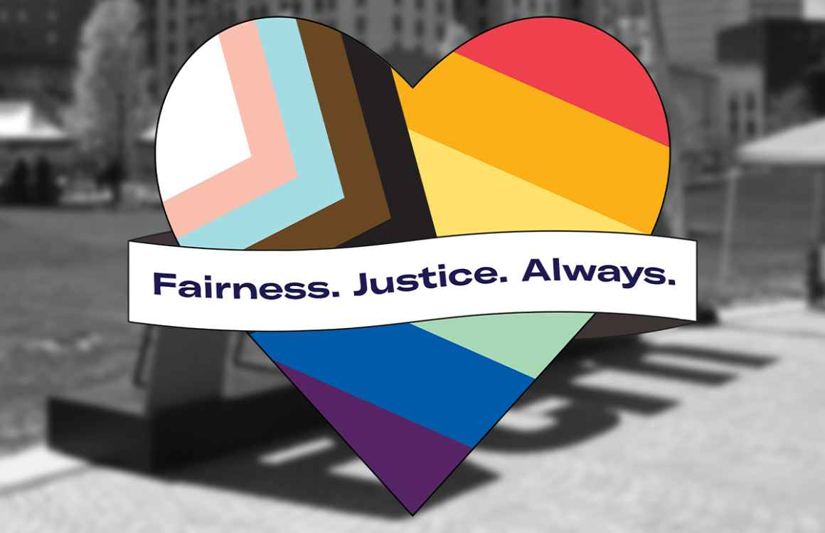 """Pride flag in the shape of a heart with a banner across the front that says """"Fairness. Justice. Always."""" on a blurred, black and white background photo."""