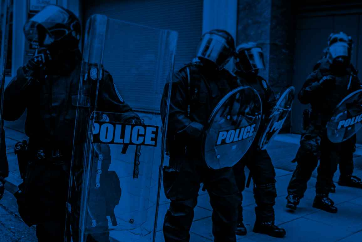 Militarized police in riot gear with a black and blue color overlay