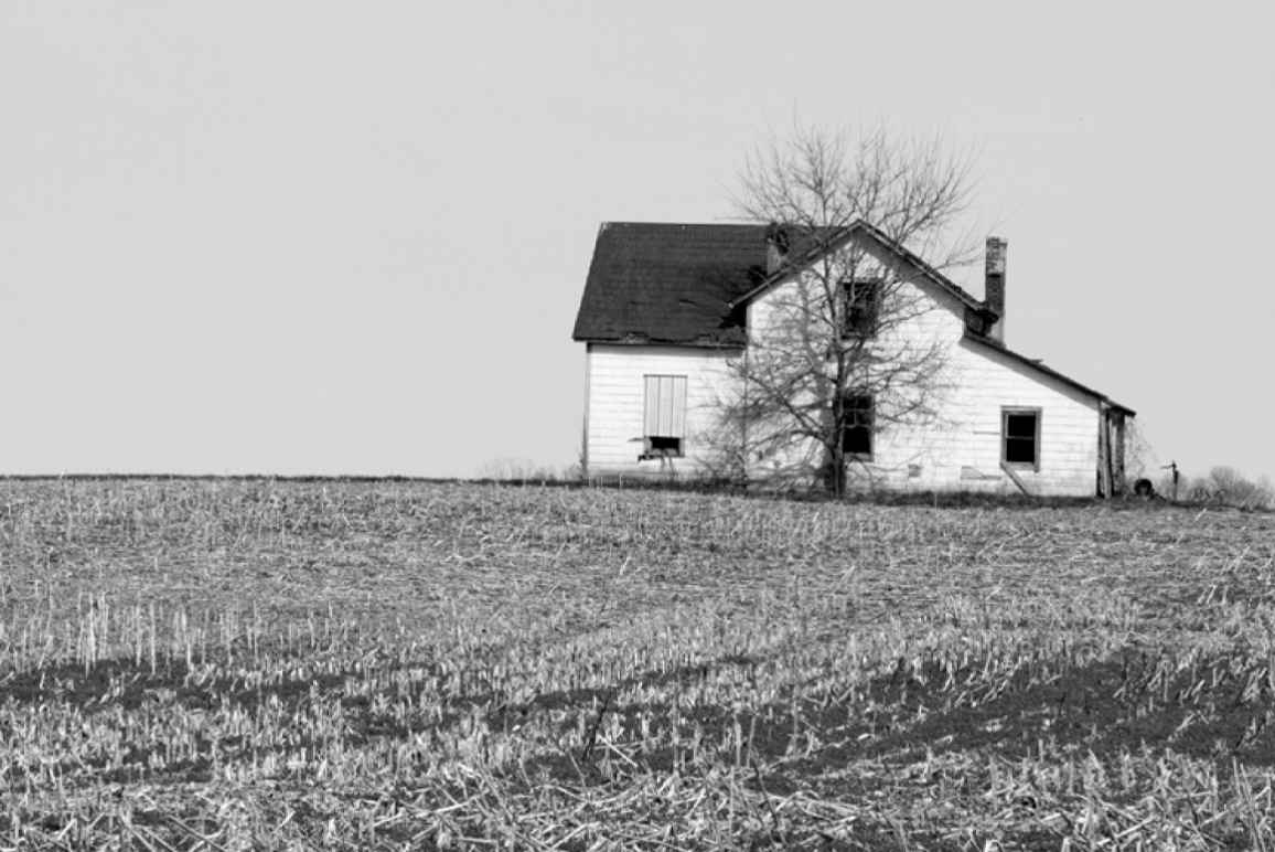 black and white photo of a white farm house in a field