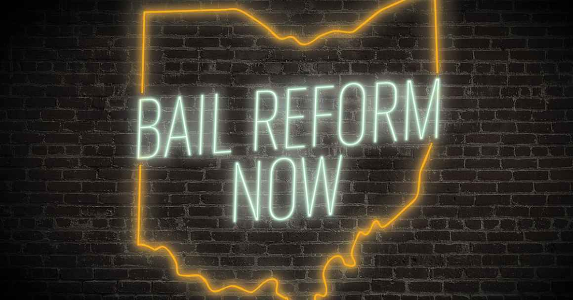 A neon sign that says 'bail reform now' in green and has an orange Ohio outline on a dark brick background