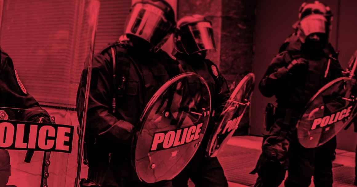 Photo of militarized police in riot gear with a black and red color overlay